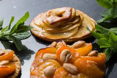 Tart with apricot and apple. Traditional french pie with fruits on dark marble background. Decorated almonds and mint. Leafs. Delicious dessert with copy space Stock Photography
