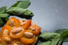 Tart with apricot. Traditional french pie with fruits on dark marble background. Decorated almonds and mint leafs. Delicious dessert with copy space closeup Stock Photos