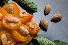 Tart with apricot. Traditional french pie with fruits on dark marble background. Decorated almonds and mint leafs. Delicious dessert with copy space closeup Royalty Free Stock Photography