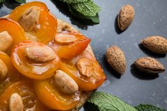 Tart with apricot. Traditional french pie with fruits on dark marble background. Decorated almonds and mint leafs. Delicious dessert with copy space closeup Royalty Free Stock Image