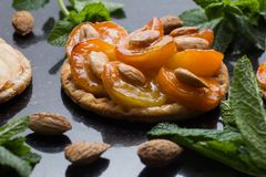 Tart with apricot. Traditional french pie with fruits on dark marble background. Decorated almonds and mint leafs. Delicious dessert with copy space closeup Royalty Free Stock Images