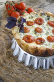 Tart with cherry tomatoes and cheese on aluminum baking dish Stock Photo