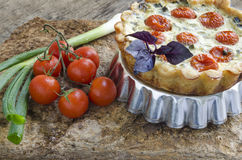 Tart with cherry tomatoes, cheese and onions on aluminum baking dish Royalty Free Stock Photo