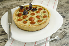Tart with cherry tomatoes, cheese and onions on white plate, near knife, fork Royalty Free Stock Image