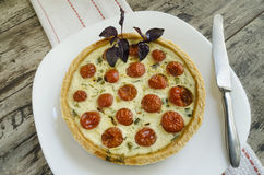 Tart with cherry tomatoes, cheese and onions on white plate, near knife Royalty Free Stock Photo