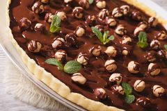 Tart with chocolate and hazelnuts on a table closeup. Horizontal Royalty Free Stock Photography