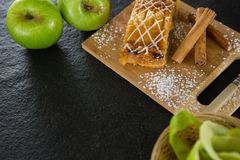 Tart and cinnamon sticks on chopping board. Close-up of tart and cinnamon sticks on chopping board Stock Image