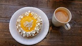 Tart and coffee on table. Yellow passion fruit tart on plate with mug of coffee on rustic wooden tabletop Royalty Free Stock Image