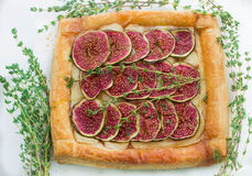 Tart with figs and Camembert. Puff pastry tart with figs, Camembert, thyme and honey Stock Photo