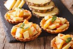 Tart filled with fresh pineapple and jam closeup. Horizontal Stock Photo