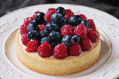 Tart with fresh berries. Close up of Homemade tart with custard, fresh raspberries and blueberries, served on white vintage plate on textile napkin over old Stock Photography