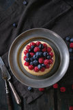 Tart with fresh berries. Homemade tart with custard, fresh raspberries and blueberries, served on vintage metal plate with fork and knife on textile napkin over Royalty Free Stock Photos