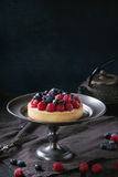 Tart with fresh berries. Homemade tart with custard, fresh raspberries and blueberries, served on vintage metal plate with iron teapot on textile napkin over old Royalty Free Stock Image