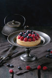 Tart with fresh berries. Homemade tart with custard, fresh raspberries and blueberries, served on vintage metal plate with iron teapot on textile napkin over old Royalty Free Stock Images