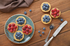 Tart with fresh raspberries and blueberries. Delicious mini tart with fresh raspberries and blueberries on wooden background Royalty Free Stock Photo
