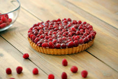 Tart with fresh raspberries on wooden background.  Royalty Free Stock Images