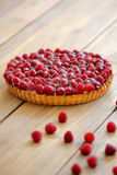 Tart with fresh raspberries on wooden background.  Stock Image