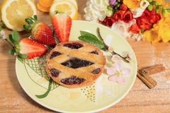 A tart with fruit jam with almond blossom,strawberry and spring flowers. Close up of a tart with fruit jam,almond blossom,strawberry,cinnamon and freesia royalty free stock photography