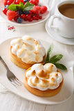 Tart with lemon curd, merengue and coffee with milk close-up. ve Royalty Free Stock Photos