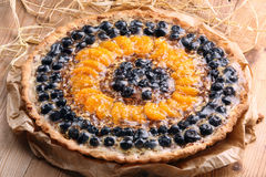 Tart with mandarins and cranberries on wooden background Stock Image