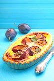 Tart of pastry with plums. On a blue background royalty free stock images