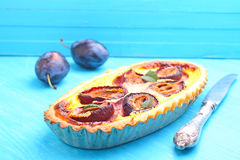 Tart of pastry with plums. On a blue background stock image