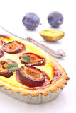 Tart of pastry with plums. On a white background royalty free stock images