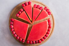 Tart, pie, cake with jellied and fresh raspberry on the light concrete background. Slice of cake Stock Image