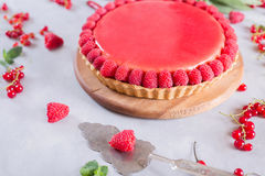 Tart, pie, cake with jellied and fresh raspberry on the light concrete background. Top view. Sweet food photo concept Stock Photography