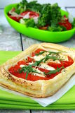 Tart of puff pastry with peppers and goat cheese stock photos