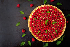 Tart with raspberries and whipped cream decorated with mint leaves on a black background. Top view Stock Photos