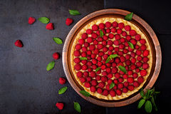 Tart with raspberries and whipped cream decorated with mint leaves on a black background. Top view Royalty Free Stock Image