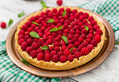 Tart with raspberries and whipped cream decorated with mint leaves. Tart with raspberries and whipped cream decorated with mint leaves on a wooden background Stock Images