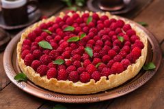 Tart with raspberries and whipped cream decorated with mint leaves. On a wooden background Stock Photography