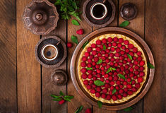 Tart with raspberries and whipped cream decorated with mint leaves on a wooden background. Top view Royalty Free Stock Photography