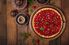 Tart with raspberries and whipped cream decorated with mint leaves on a wooden background. Top view Stock Images