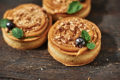 Tart with salted caramel french dessert. Food industry, mass or volume production. Dessert on wooden background stock images