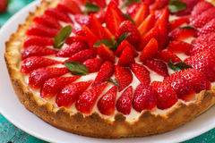 Tart with strawberries. And whipped cream decorated with mint leaves Stock Photography