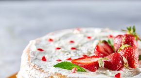 Tart with strawberries and whipped cream decorated with mint leaves on white textured background, selective focus. Tart with strawberries and whipped cream stock images
