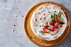 Tart with strawberries and whipped cream decorated with mint leaves on white textured background, selective focus. Tart with strawberries and whipped cream royalty free stock photo