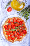 Tart with tomatoes and herbs. On white plate Stock Photography