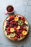 Tart with whipped cream, mixed fruit and a jar with maple syrup Royalty Free Stock Photography