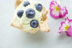 Tarta con los arándanos y las flores en la tabla azul imagen de archivo libre de regalías