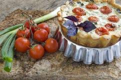 Tarta con los tomates, el queso y las cebollas de cereza en el plato de aluminio de la hornada Foto de archivo libre de regalías