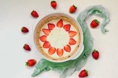 Tarta cruda de la fresa en el fondo blanco de la cocina Pastel de queso de las bayas adornado con las fresas y la menta frescas o imagen de archivo libre de regalías