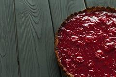 Tarta de frambuesa cruda sana deliciosa de la comida y de las frambuesas de la almendra en el fondo de madera oscuro, espacio lib Fotografía de archivo libre de regalías