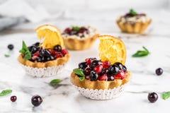 Tarta de la fruta con la naranja, granada, pasa y crema, tortas y dulzor en fondo de mármol ligero Postre delicioso fotografía de archivo