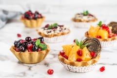 Tarta de la fruta con la naranja, granada, pasa y crema, tortas y dulzor en fondo de m?rmol ligero Postre delicioso fotos de archivo libres de regalías