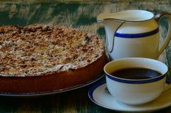 Tarta de la migaja del ciruelo con la taza de café y de desnatadora en fondo verde Imagen de archivo