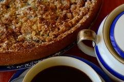 Tarta de la migaja del ciruelo con la taza de cuenco del café y de azúcar en fondo rojo Foto de archivo libre de regalías